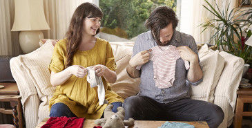 Couple sitting on sofa looking at baby clothes