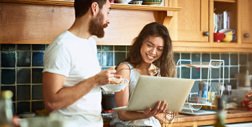 Couple standing in kitchen looking at laptop screen