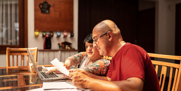 Couple doing paperwork together at home using laptop