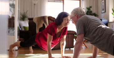 Elderly couple exercising on living room floor