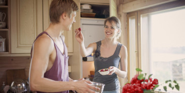 Couple sharing fruit in kitchen
