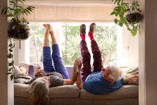 Elderly couple on sofa with legs up