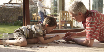Grandparent and grandchild on floor counting coins