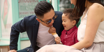 Parents and young child outside eating icecream