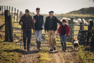 Family of farmers walking along a track with a dog following closely