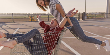Friends pushing each other in shopping cart trolley