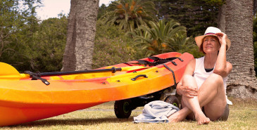 Person sitting on grass next to kayak and palm trees