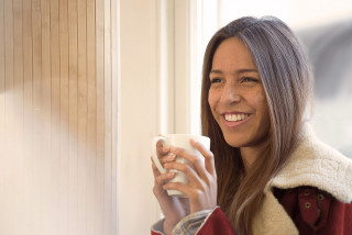 Person smiling with warm mug of tea