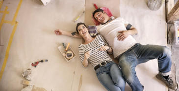 Couple taking a break from painting home and laughing on floor