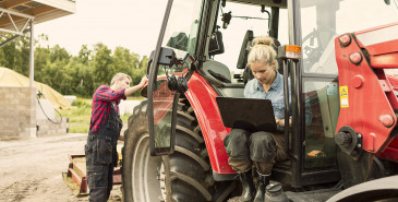 Two farm workers, one sitting in tractor using laptop while other stands by
